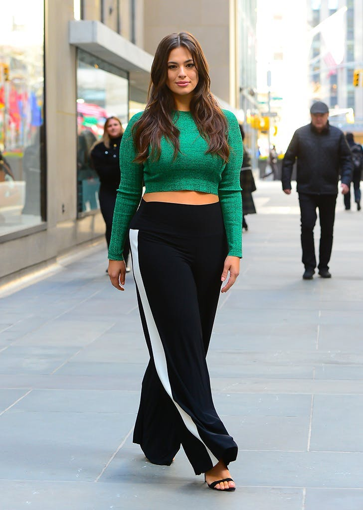 Ashley Graham в широких черных брюках с лампасами и зеленом кроп топе