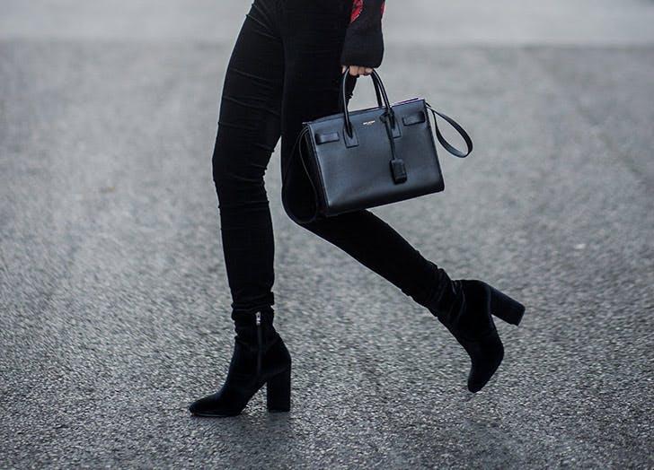 Девушка в черных джинсах скинни и замшевых ботильонах