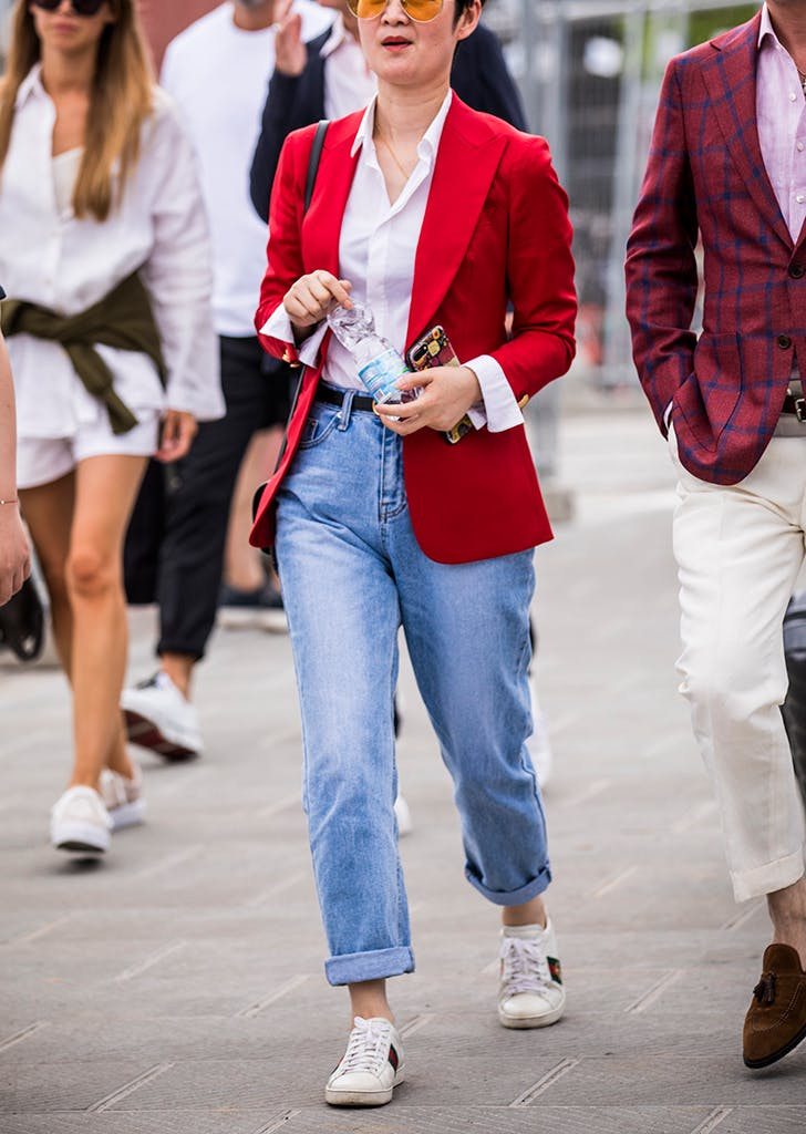 Девушка в голубых мом джинсах и красном пиджаке