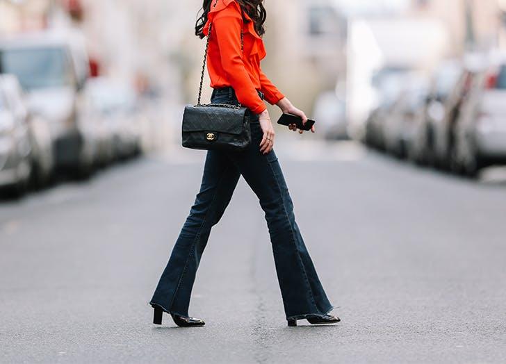 Девушка в кожаных ботильонах и джинсах клеш