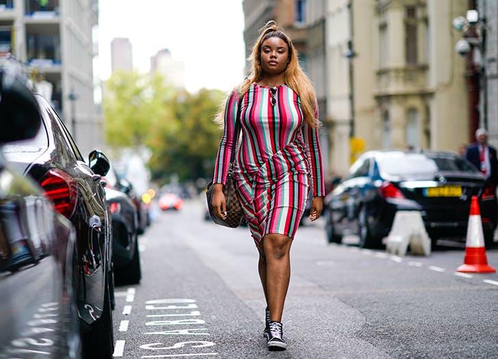 Девушка в облегающем платье в яркую полоску и кедах