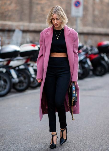 Девушка в розовом пальто, черных джинсах скинни и кроп топ
