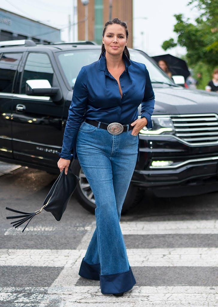 Девушка в синих джинсах клеш и синей шелковой блузке