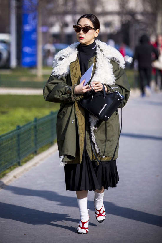 Девушка в удлиненной парке, черной мини юбке и водолазке