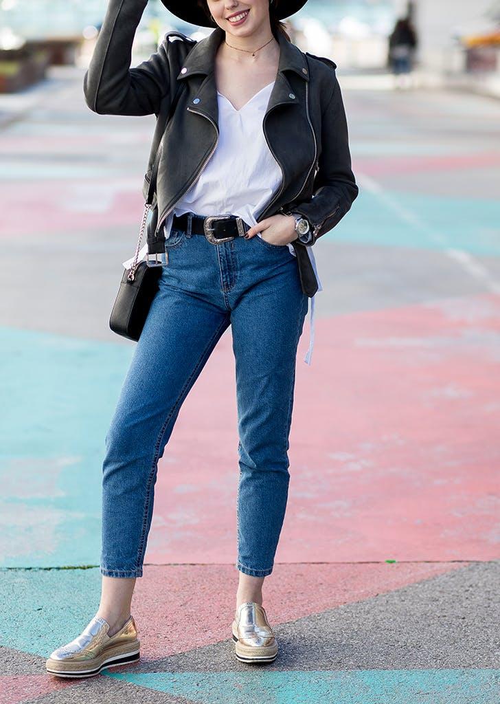 Девушка в укороченных джинсах, белый топ и куртка косуха