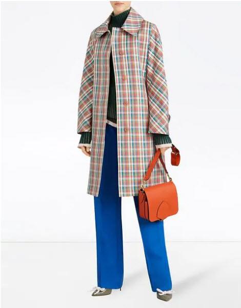 Модель в прямом пальто в клетку и синих брюках