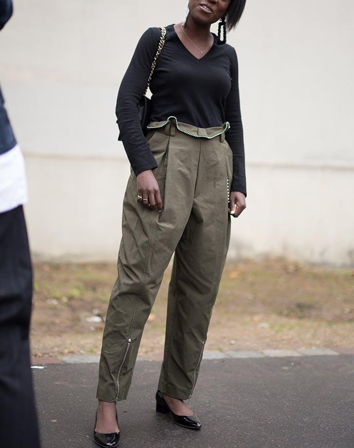 Модель в серых брюках с высокой талией и черной водолазке
