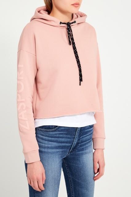 Модель в синих джинсах и розовой толстовке с капюшоном