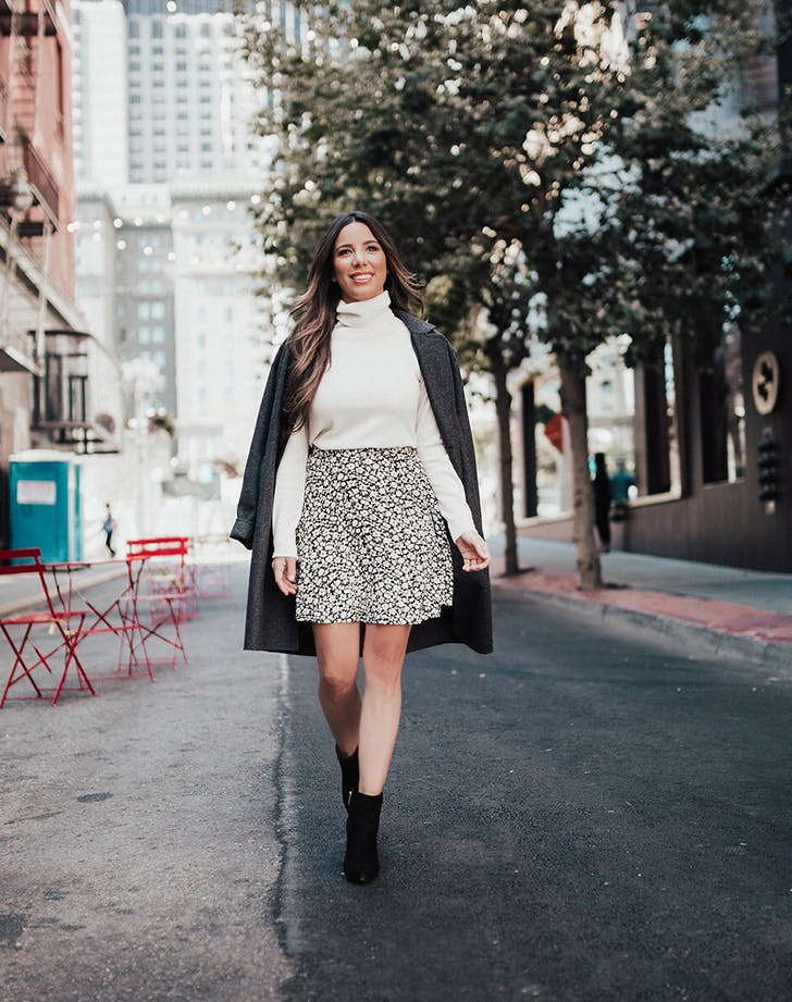 Ariana Lauren в белой водолазке, пестрой мини юбке, серое пальто