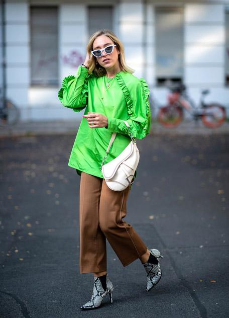 Девушка в брюках кюлотах, зеленая блузка и ботильоны