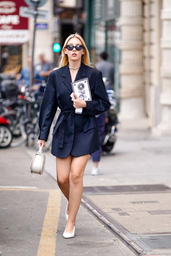 Девушка в черном мини платьк с длинными рукавами и белые туфли