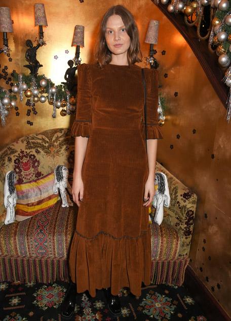 Девушка в коричневом вязанном платье макси с белыми кроссовками