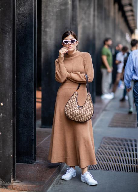 Девушка в коричневом вязанном платье макси с блыми кроссовками