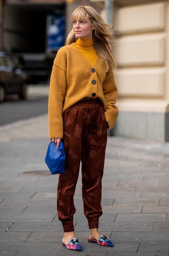 Девушка в коричневых штанах и желтом кардигане, синяя сумка
