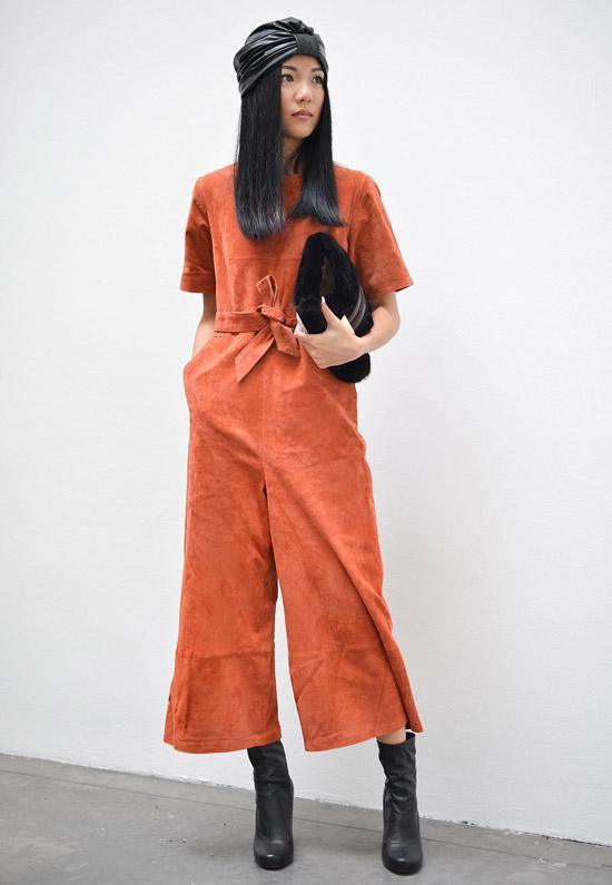 Девушка в оранжевом комбинезоне, черные ботильоны и платок на голове
