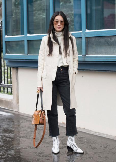 Девушка в прямых черных джинсах, светлый плащ и ботильоны