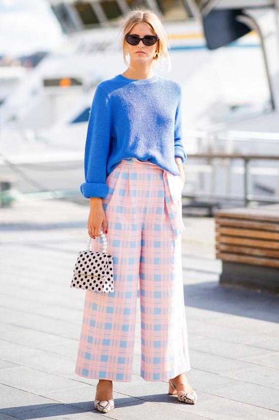 Девушка в светлыю брюках в клетку и синем свитере