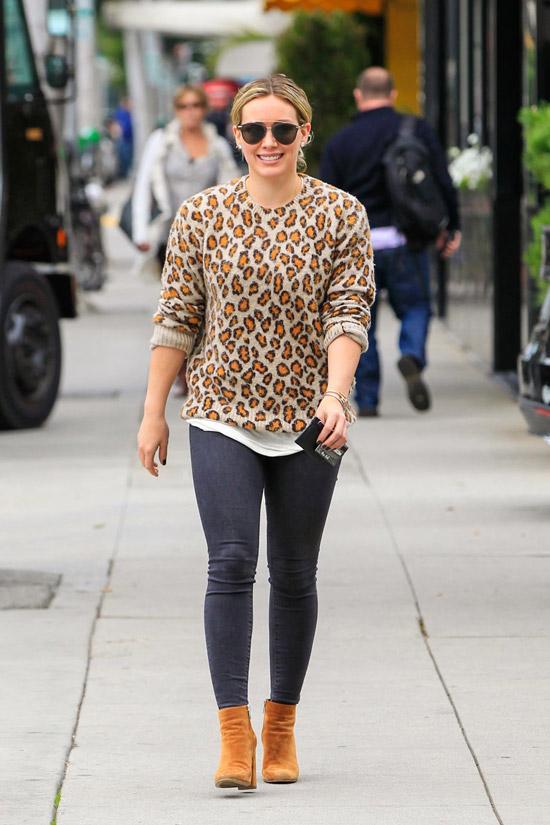 Девушка в темных джинсах скинни, леопардовом свитере и ботильонах