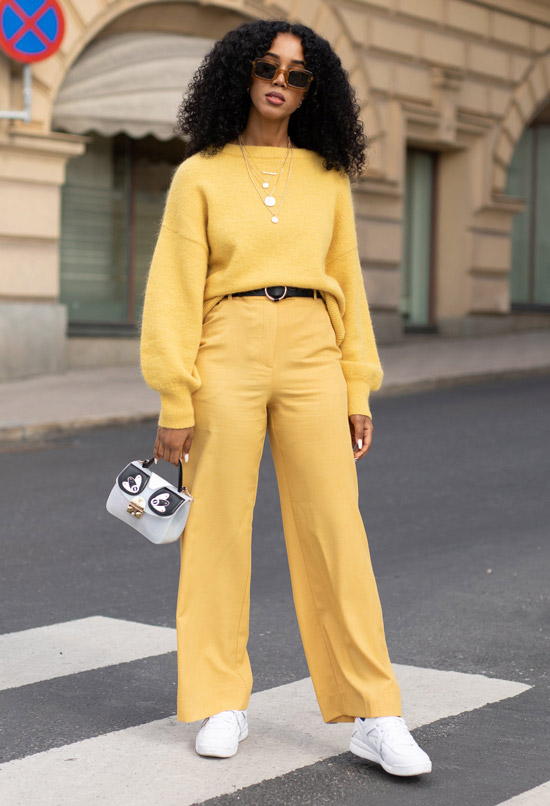 Девушка в желтых брюках палаццо, желтый свитер и белые кроссовки