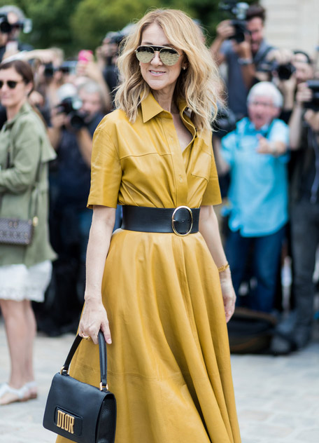 Селин Дион в желтом кожаном платье миди с черным поясом и черной сумкой