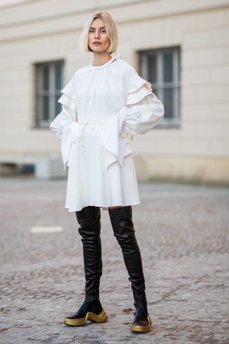 Девушка в белом платье и черных ботфортах без каблука
