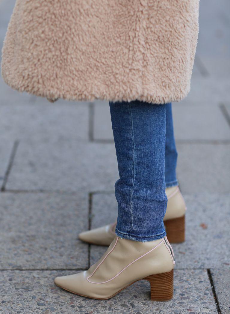 Девушка в бежевых ботильонах на низком каблуке и джинсы