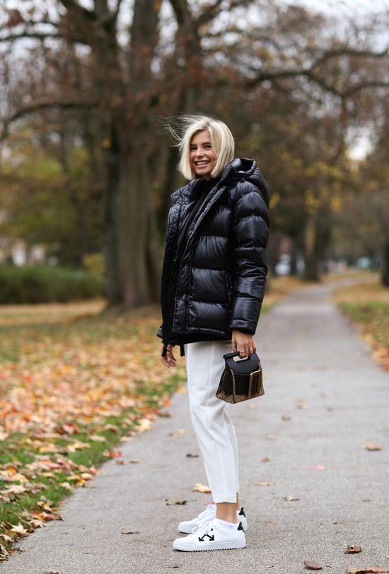 Девушка в черном пуховике оверсайз и белых брюках
