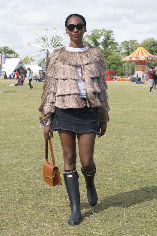 Девушка в черной мини юбке, кофта с бахромой и черные сапоги