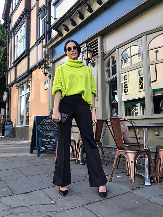 Девушка в черных брюках и желтом свитере