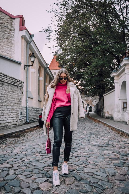 Девушка в черных брюках, розовый свитер и бежевое пальто