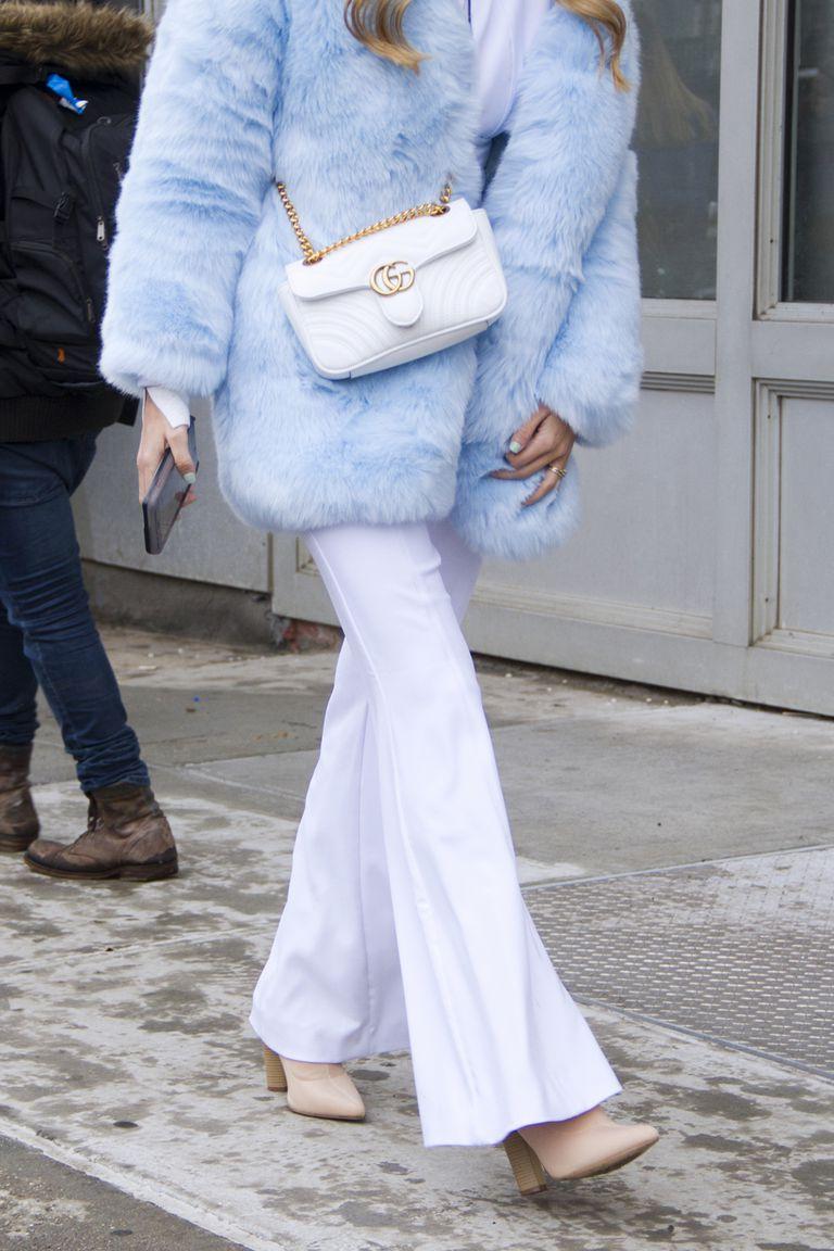 Девушка в голубой шубе, белые брюки клег и бежевые сапоги