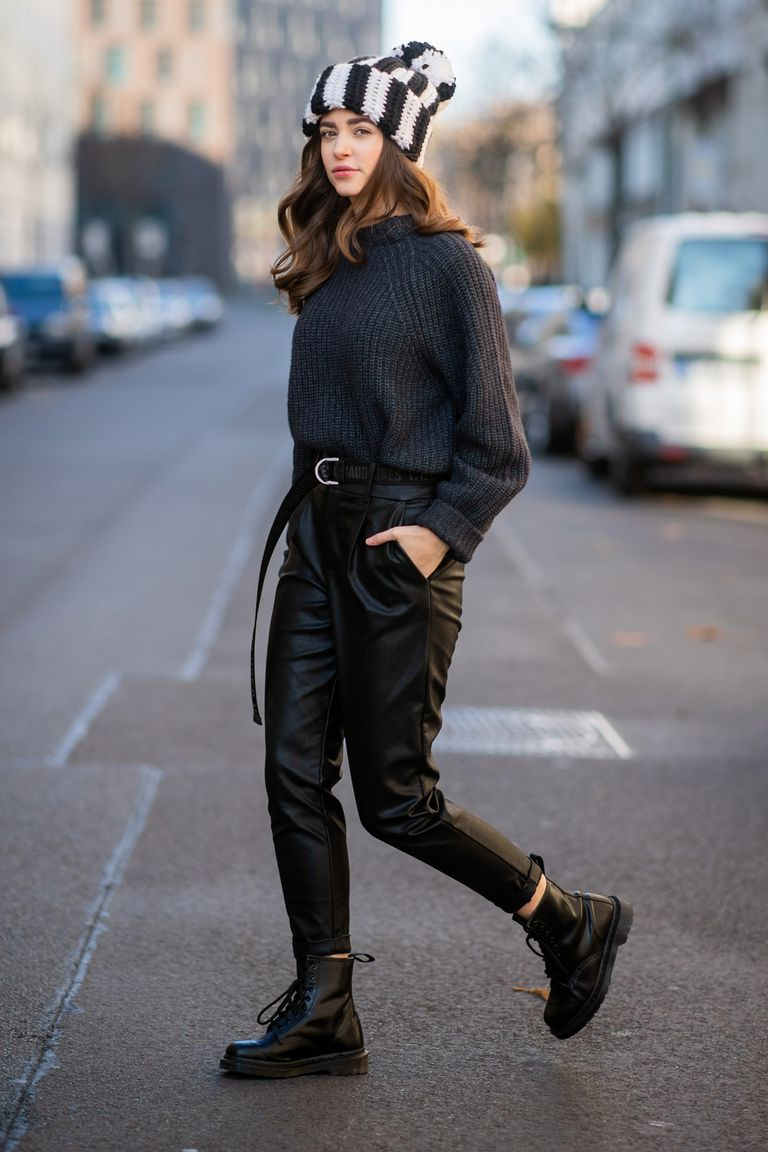 Девушка в кожаных черных брюках, свитер и ботинки на шнурках