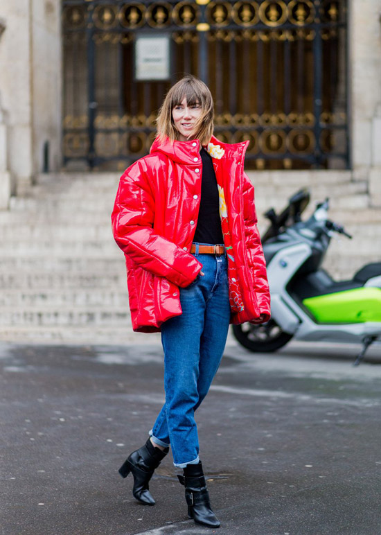 Девушка в красном пуховике оверсайз и синих джинсах