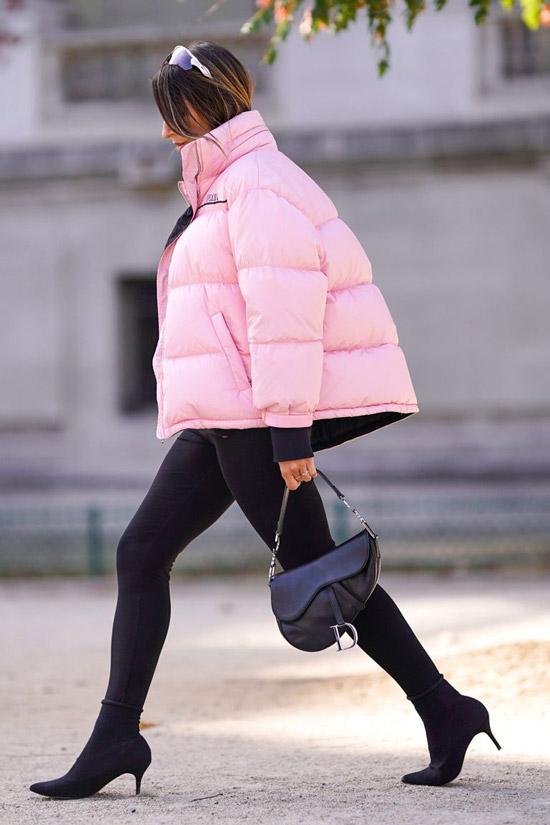 Девушка в объемном розовом пуховике, черные лосины и ботильоны