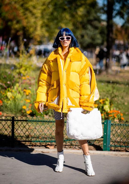 Девушка в объемном желтом пуховике, белые ботильоны и сумка