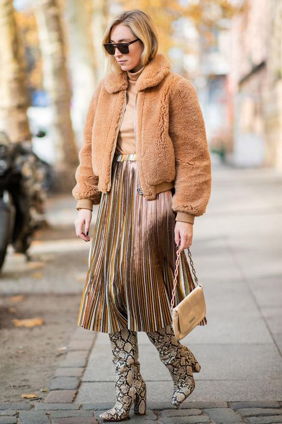 Девушка в плиссированной юбке мини, бежевая куртка и сапоги из змеиной кожи