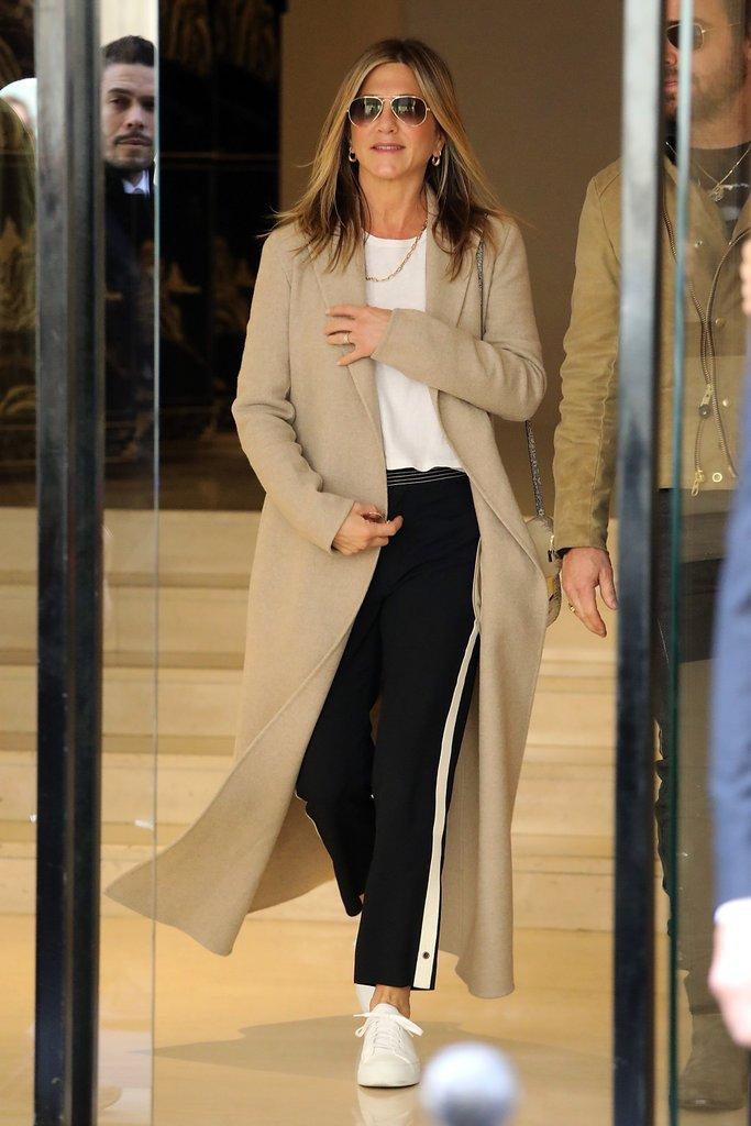 Дженнифер Энистон в бежевом пальто, черные джинсы и белая футболка