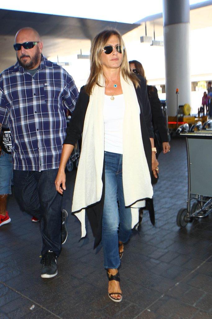 Дженнифер Энистон в черно белом крдигане и джинсах