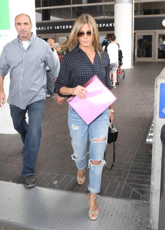 Дженнифер Энистон в черной блузке в горошек и голубых рваных джинсах