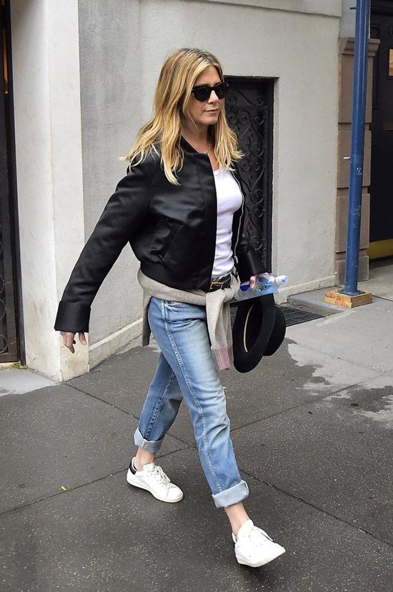 Дженнифер Энистон в простых джинсах, черной бомбер и кеды