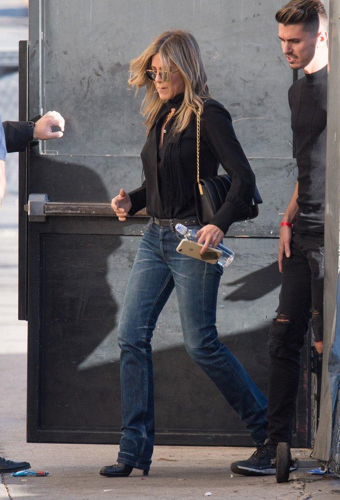 Дженнифер Энистон в синих джинсах, черная блузка и сумочка