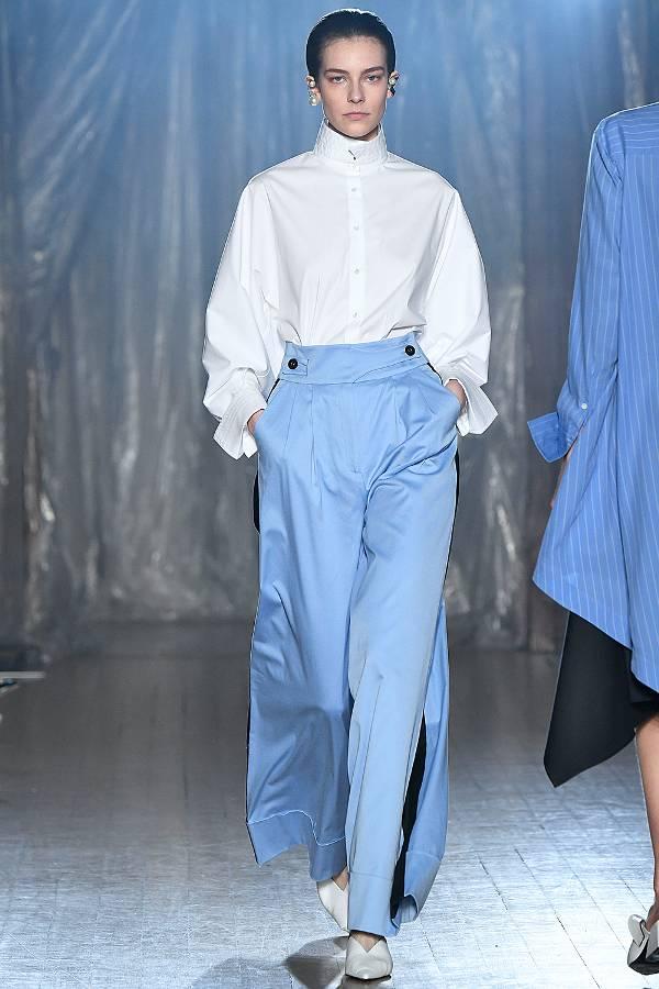 Модель в белой рубашке и голубых брюках палаццо
