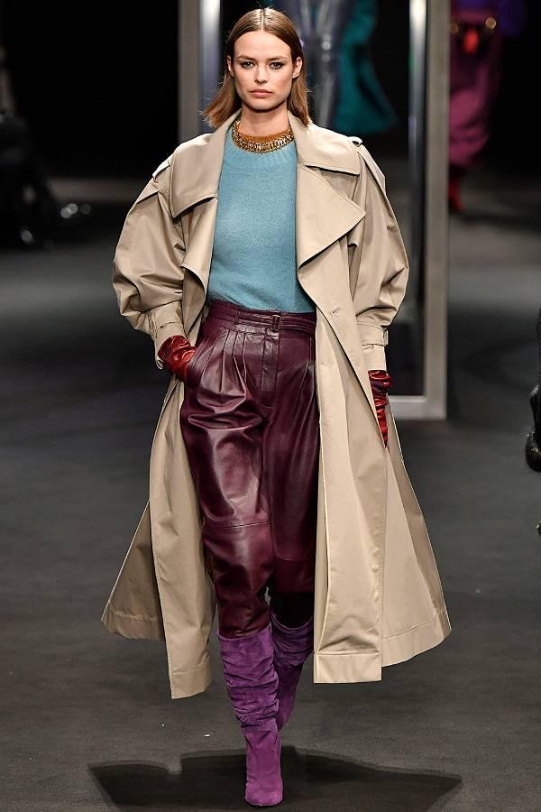 Модель в бордовых брюках, бежевый плащ и фиолетовые сапоги