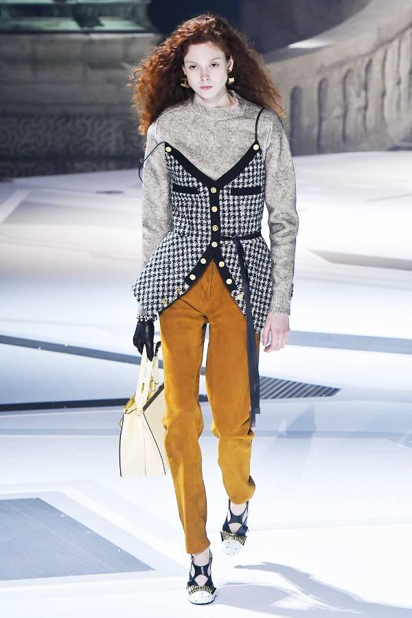 Модель в брюках горчичного цвета, серая водолазка и топ