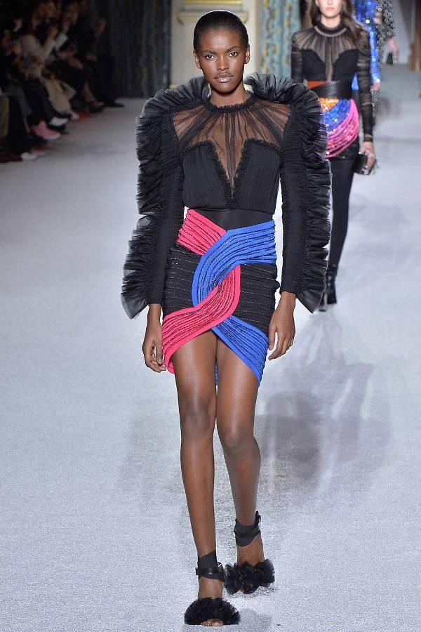 Модель в черном платье в объемными плечами