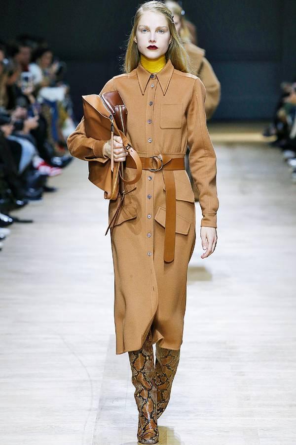 Модель в коричневом платье с ремнеи и сапогах со змеинным принтом
