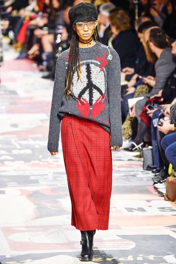 Модель в красной длинной юбке и сером свитере с принтом