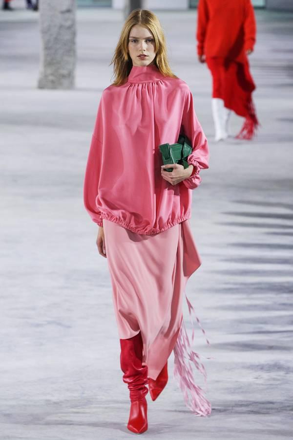 Модель в розовой юбке и блузке и красные сапоги