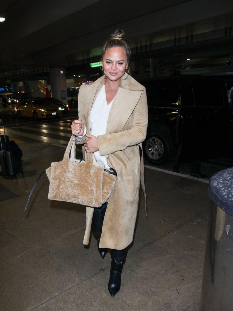 Chrissy Teigen в белом свитере и бежевом пальто