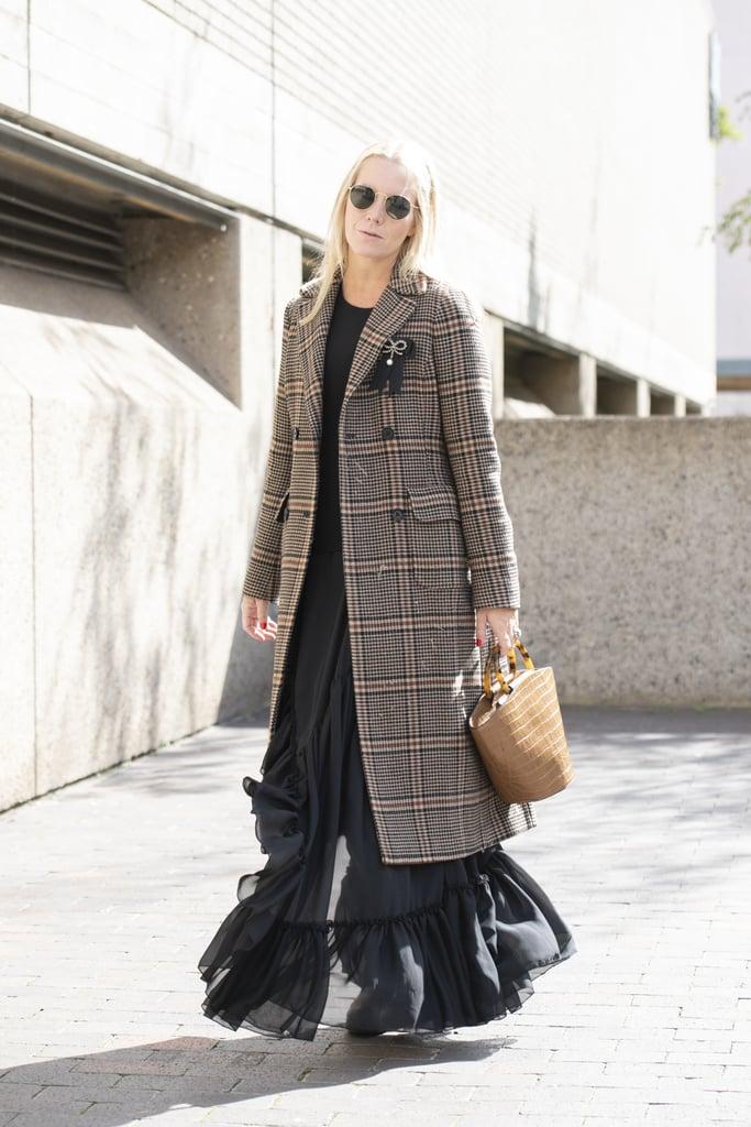 Девушка в черном платье макси и клетчатое пальто